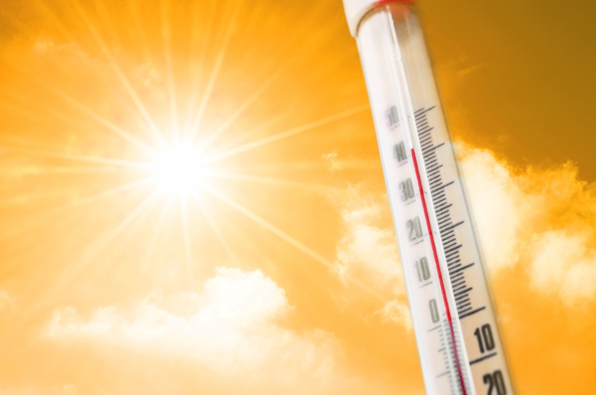 Thermometer against the background of an orange yellow hot glow of clouds and sun, concept of hot weather